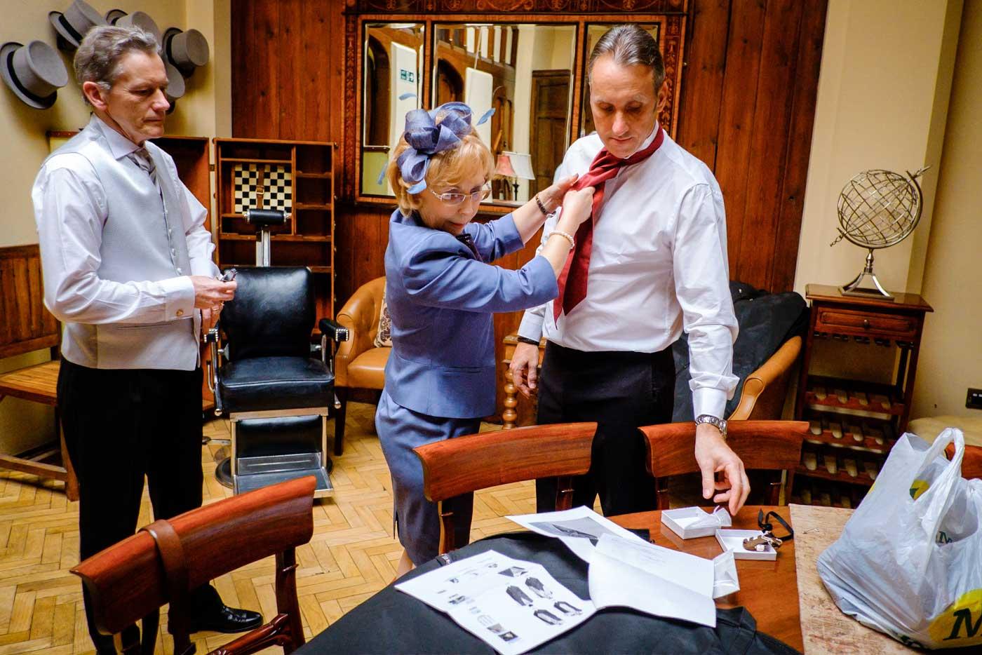 Groom's mother-in-law helping groom to tie his cravat