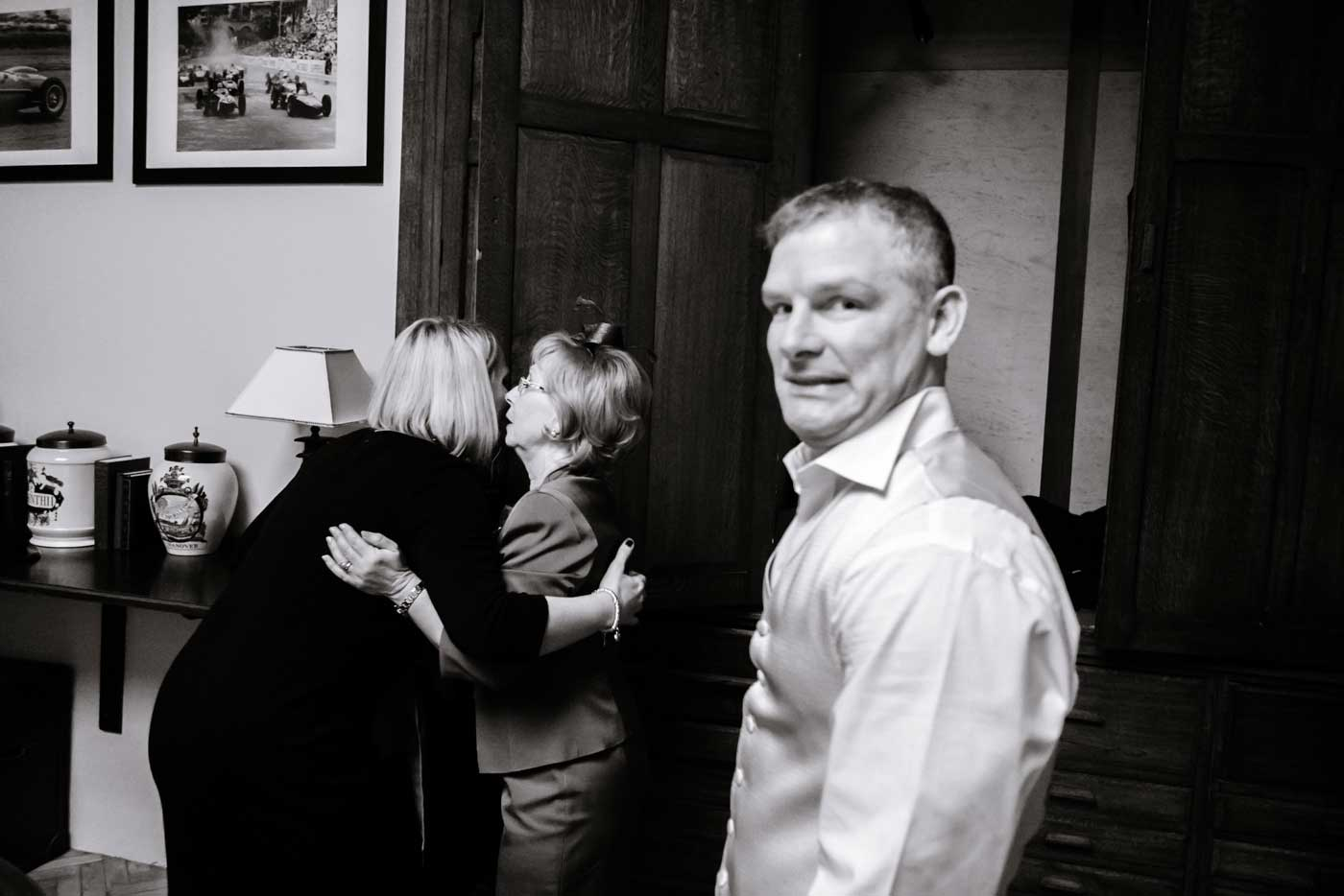 Women hugging at Stanbrook Abbey with bestman in foreground with funny expression on his face