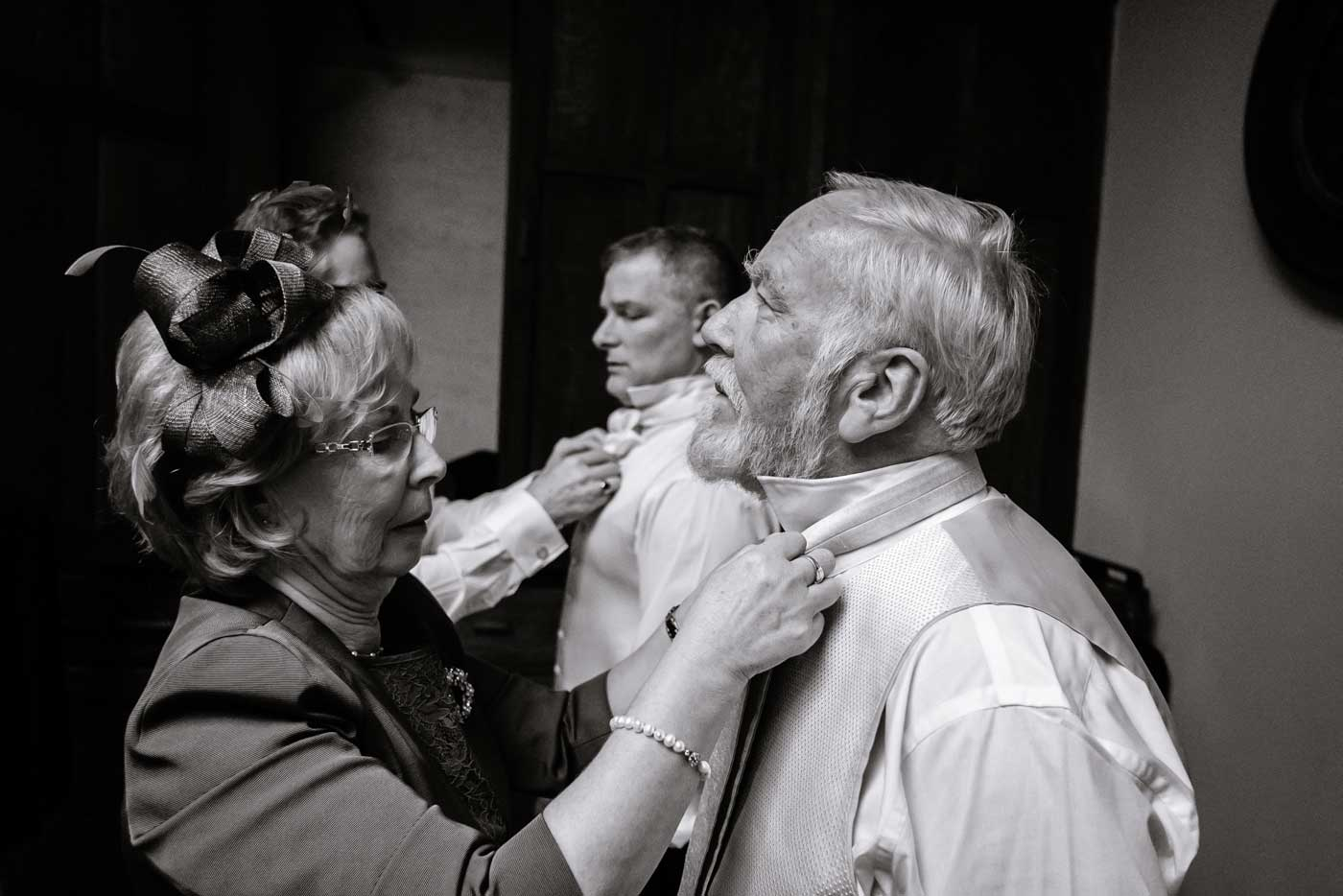 Men having their cravats tied at Stanbrook Abbey by Stanbrook Abbey wedding photographer Clive Blair Photography