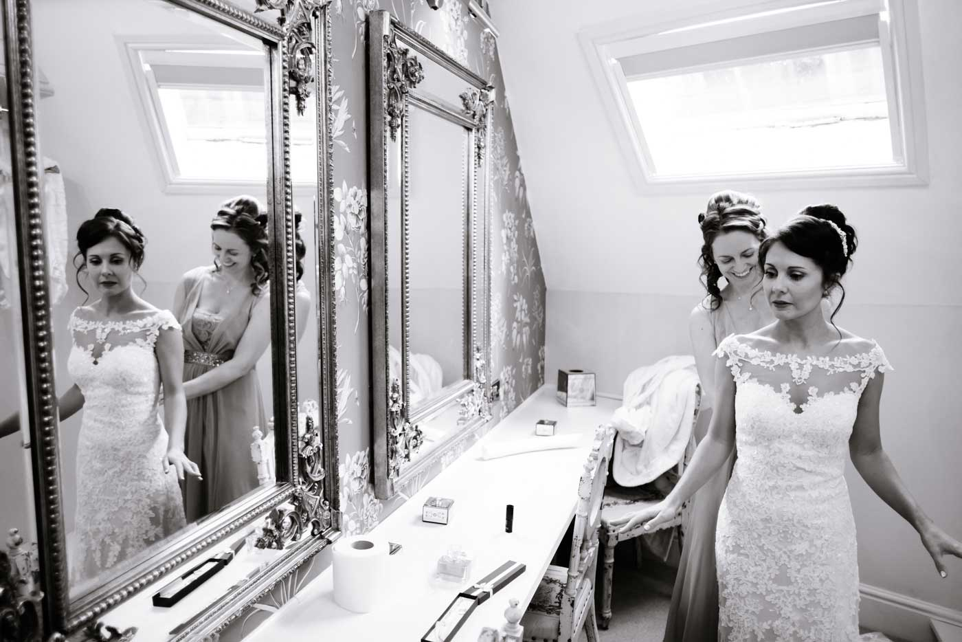 Bride having her dress tied up by maid