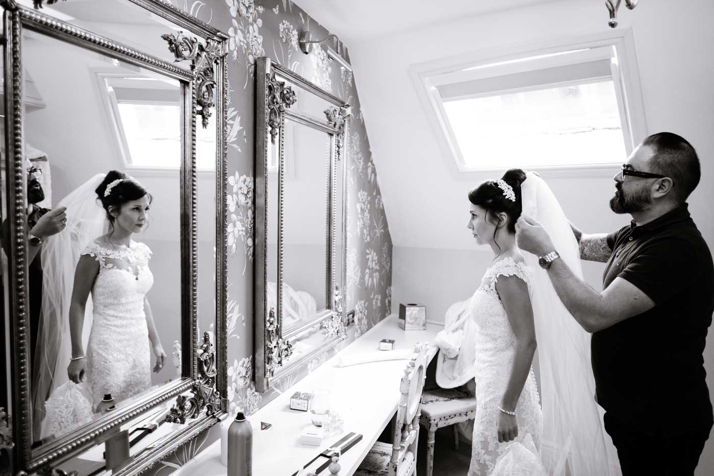 Bride's veil being put on as photographed by Stanbrook Abbey wedding photographer Clive Blair Photography