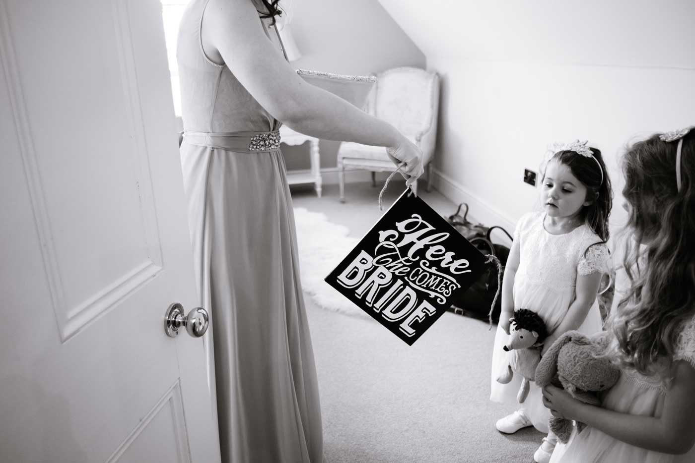 Maids being given a Here Comes the Bride sign