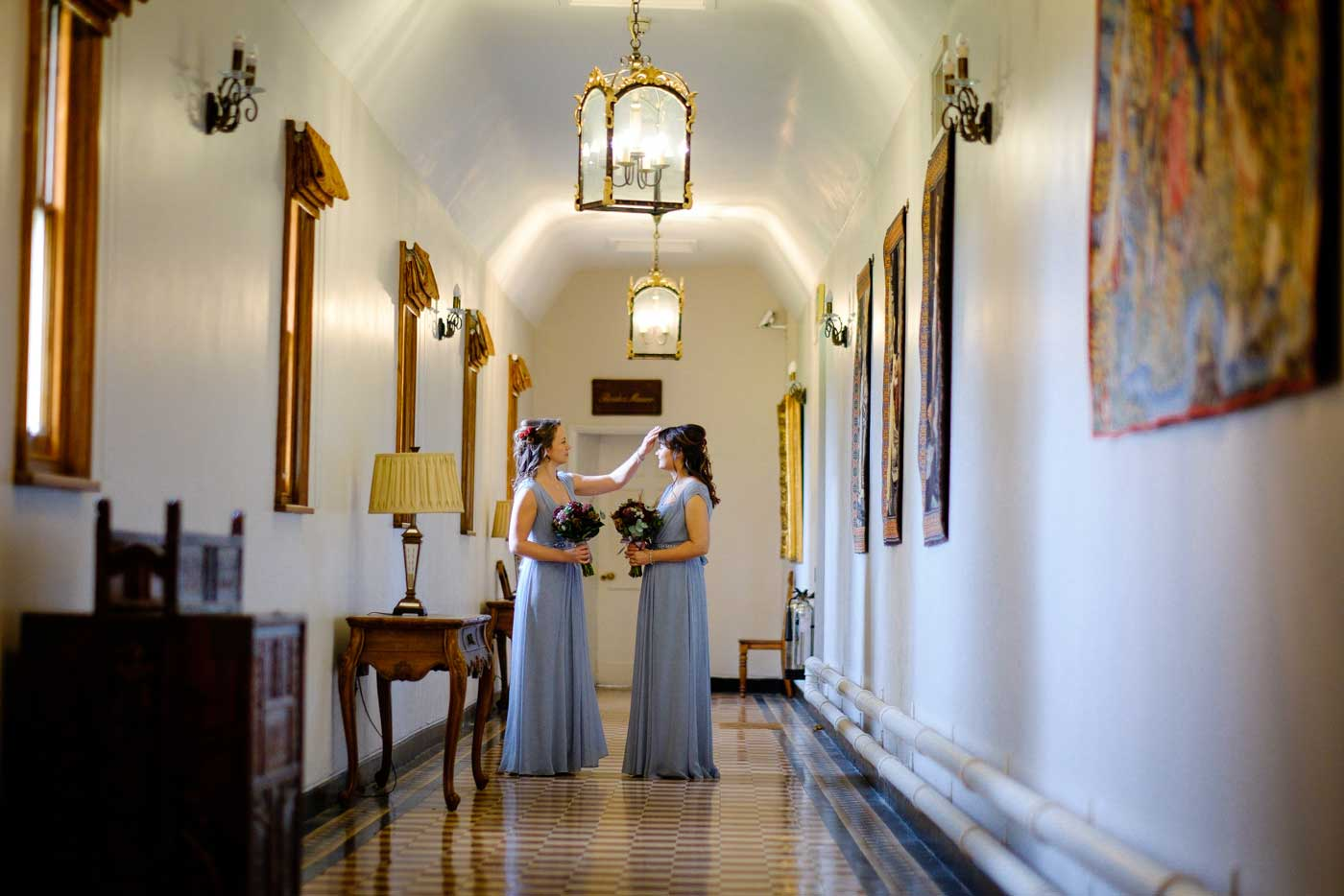 maids getting fianl adjutments in hallway on the way to a Stanbrook Abbey wedding ceremony