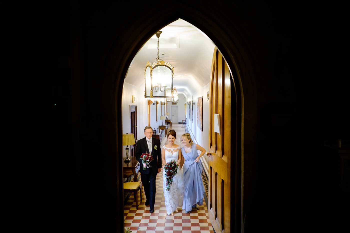 Bride, father and maid on the way to wedding ceremony by Stanbrook Abbey wedding photographer Clive Blair Photography