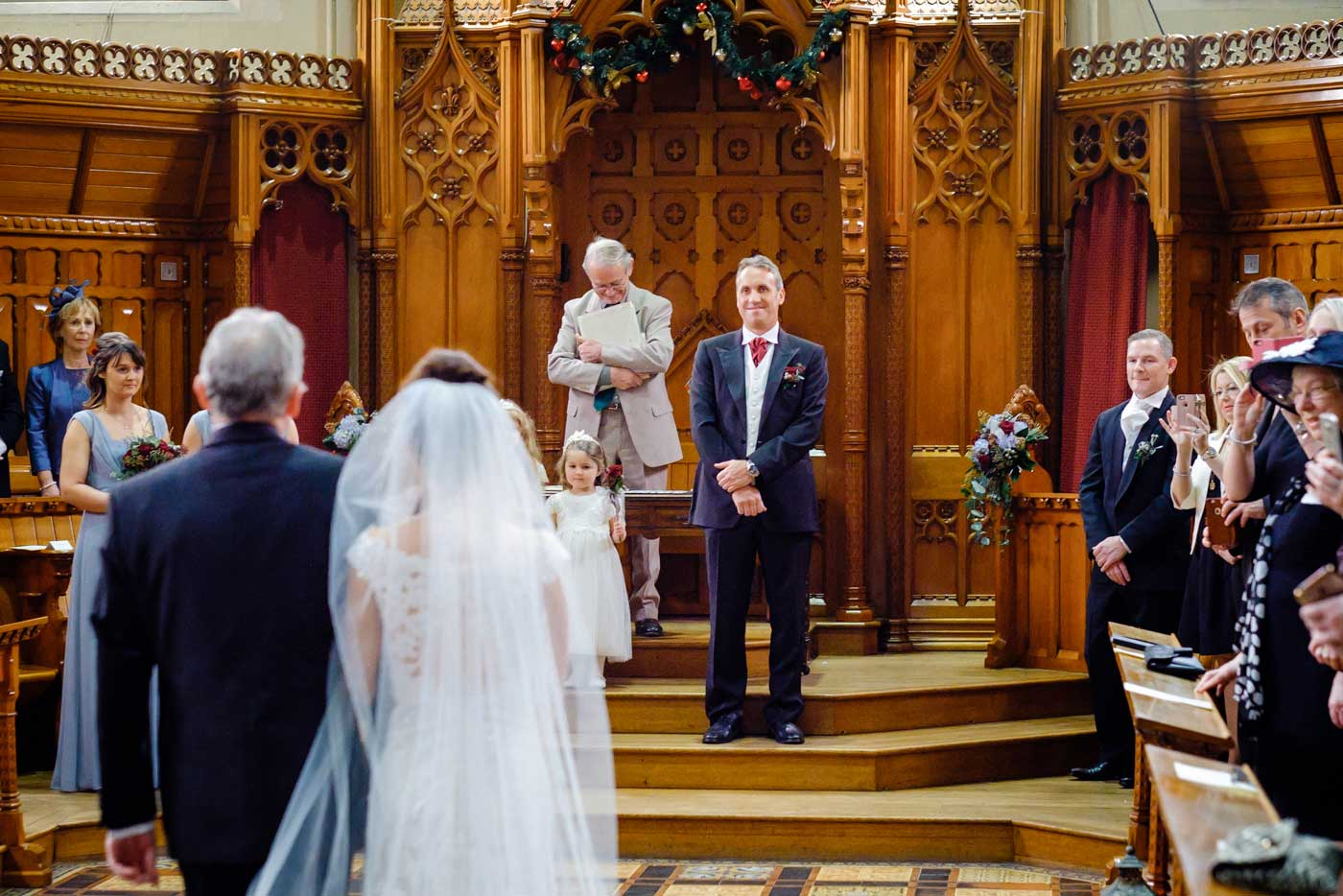 Proud groom watching his bride enter The Callow Great Hall at Stanbrook Abbey by Stanbrook Abbey wedding photographer Clive Blair Photography