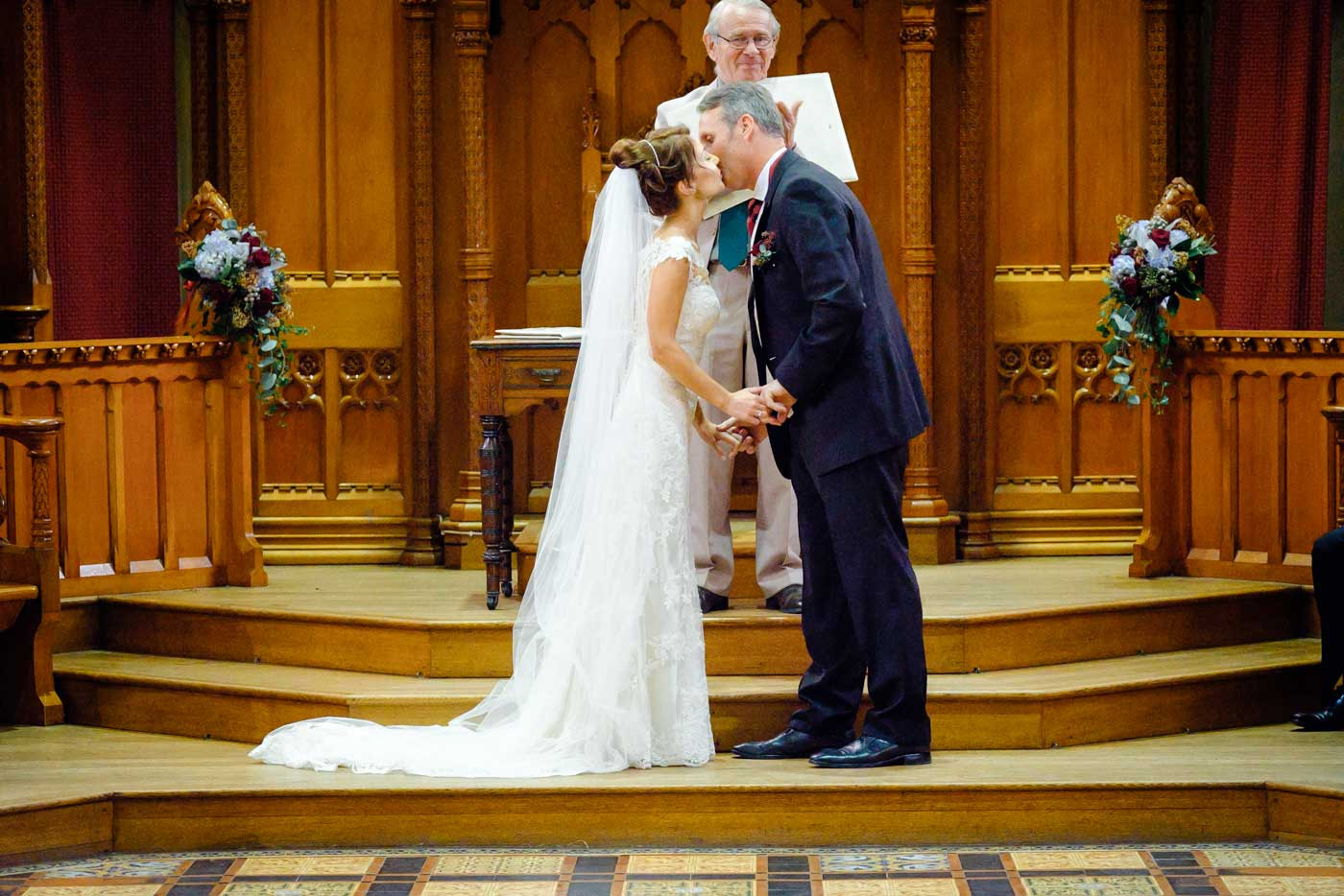 Groom and bride kissing after their wedding ceremony at The Callow Great Hall at Stanbrook Abbey by Stanbrook Abbey wedding photographer Clive Blair Photography