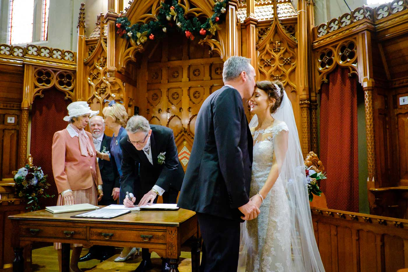 Groom kissing bride on forehead during signing the registers at The Callow Great Hall in Stanbrook Abbey by Stanbrook Abbey wedding photographer Clive Blair Photography