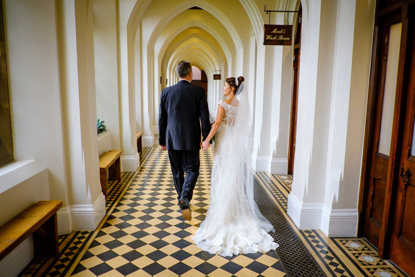 Bride and groom walking in the corridors of Stanbrook Abbey