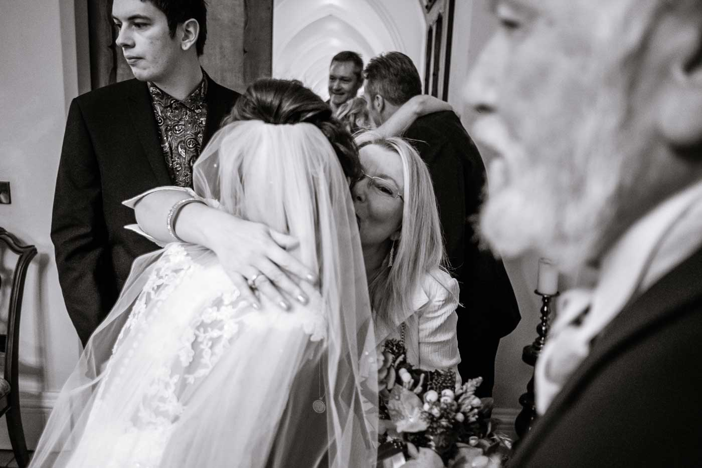 Woman hugging bride by Stanbrook Abbey wedding photographer Clive Blair Photography