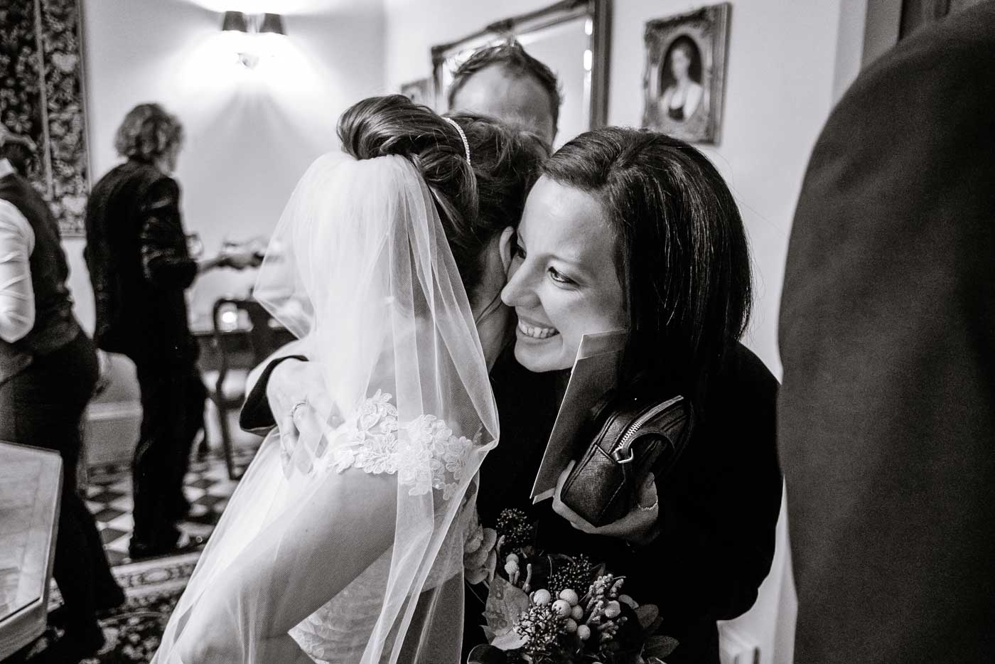 Bride being hugged by wedding guest by Stanbrook Abbey wedding photographer Clive Blair Photography