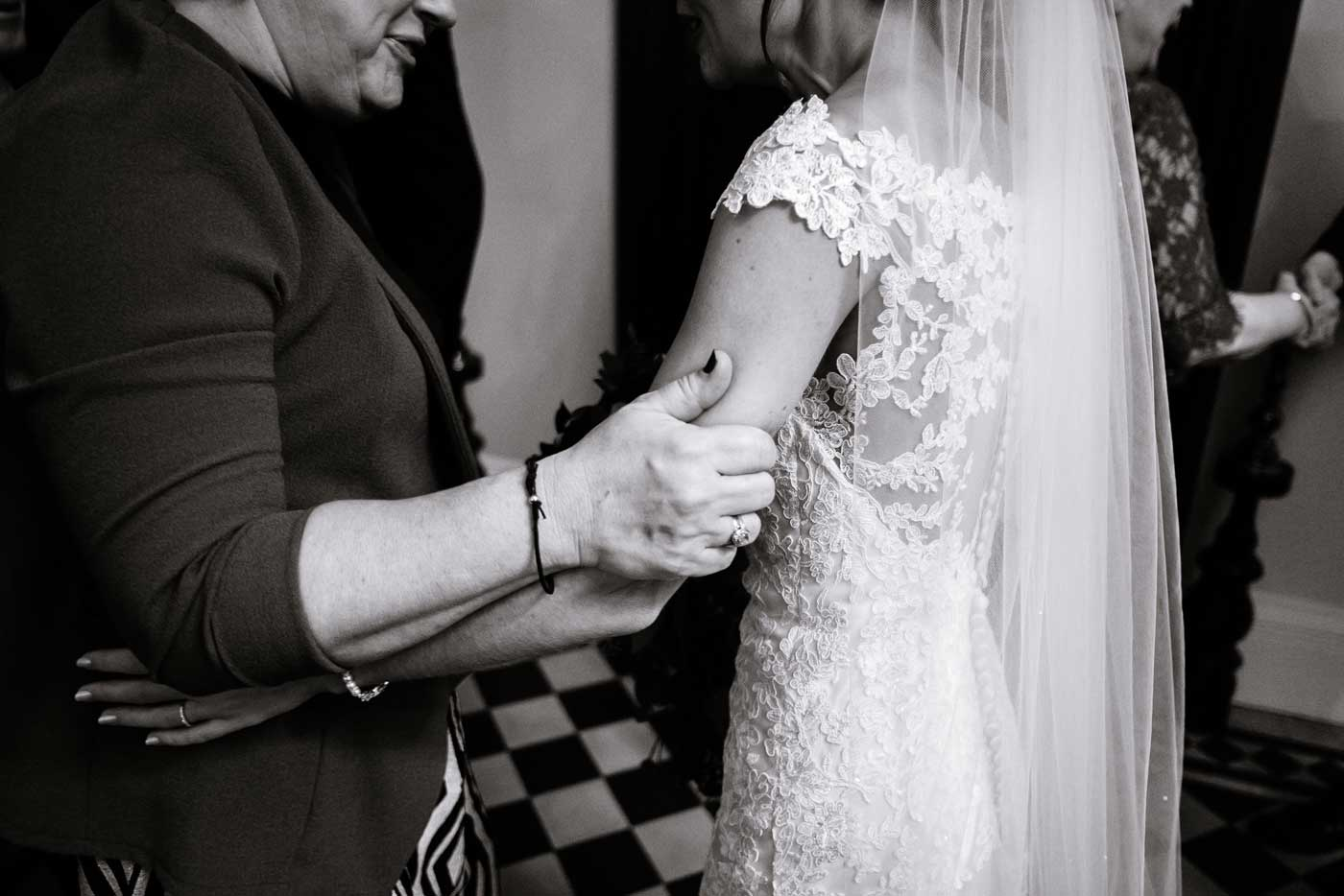 Bride being given tender squeeze on her arm by wedding guest by Stanbrook Abbey wedding photographer Clive Blair Photography