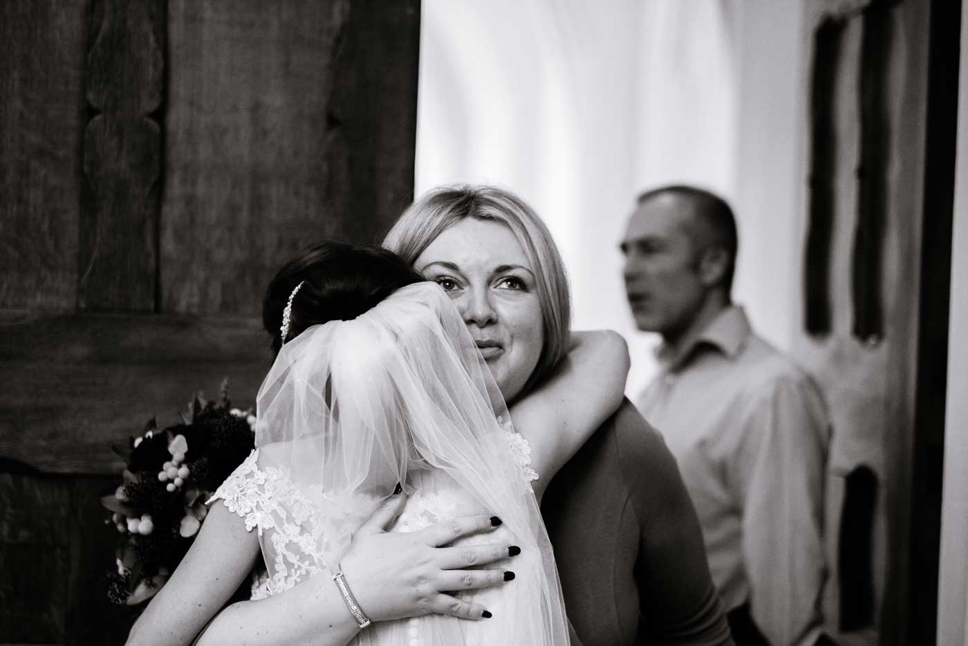 Tearful guest hugging bride after her Stanbrook Abbey wedding