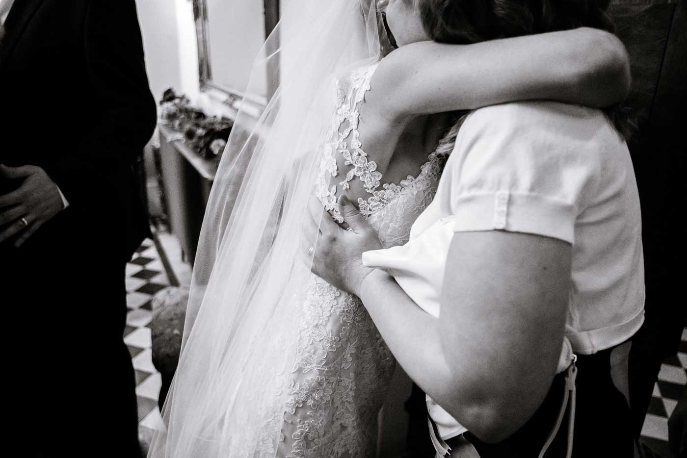 Bride being hugges by wedding guest at Stanbrook Abbey