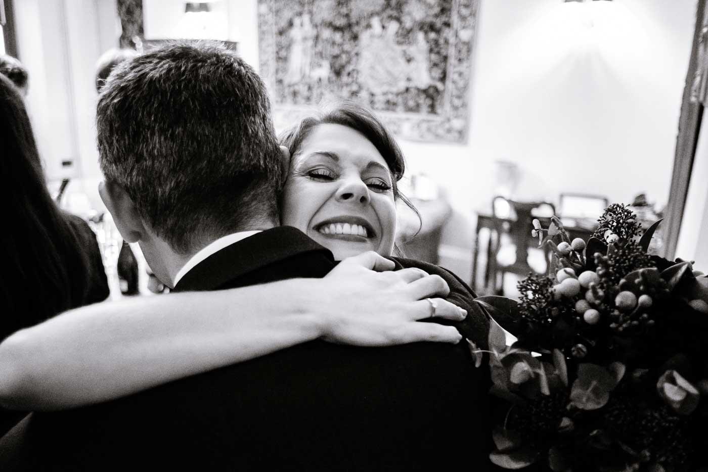 Very happy bride hugging male guest