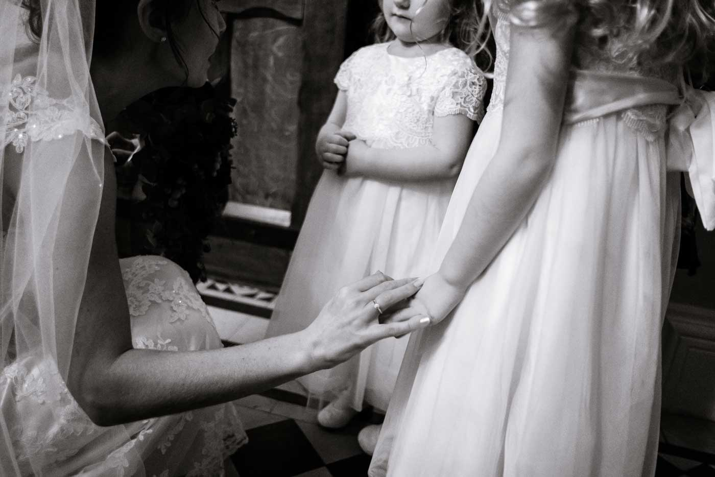 Bride giving tender touch on arm of flowergilr's arm by Stanbrook Abbey wedding photographer Clive Blair Photography
