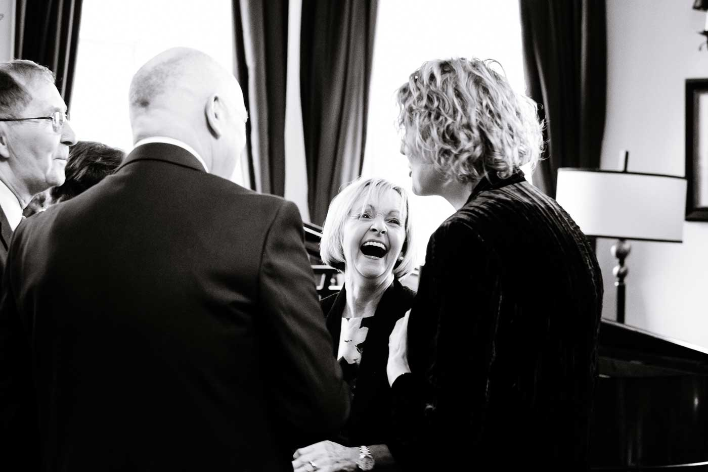 Woman laughing during the drinks reception by Stanbrook Abbey wedding photographer Clive Blair Photography