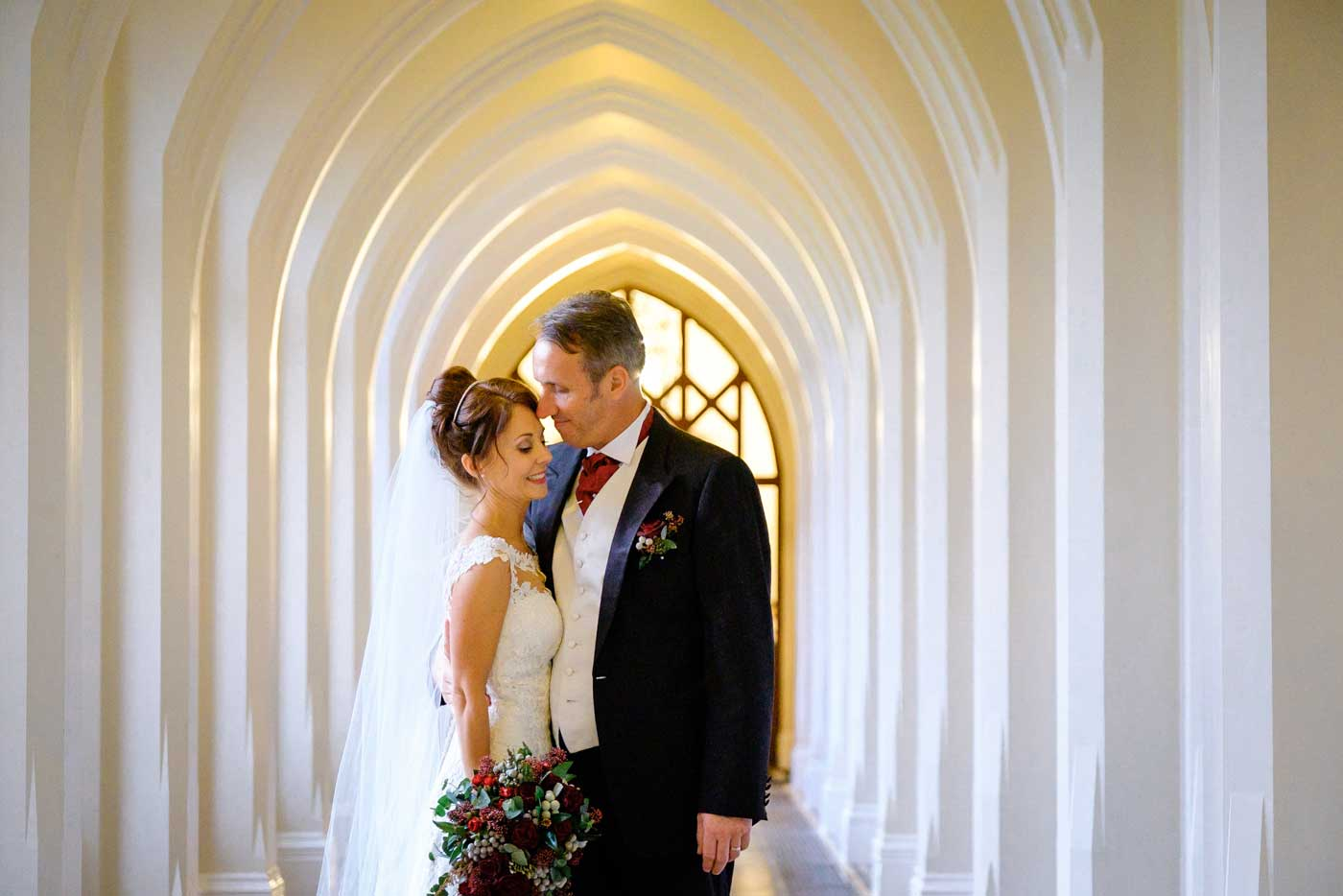 Bride and groom together in the corridor by Stanbrook Abbey wedding photographer Clive Blair Photography