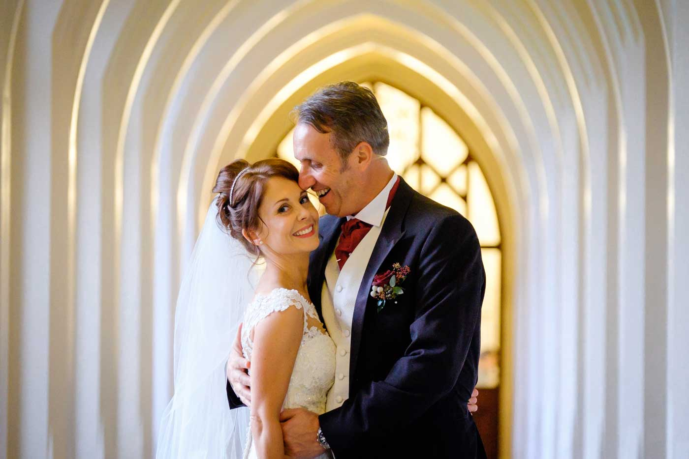 Groom hugging bride in the corridor by Stanbrook Abbey wedding photographer Clive Blair Photography