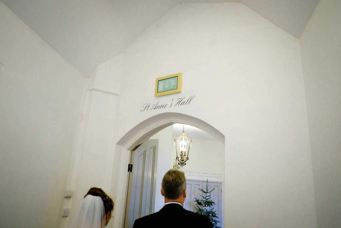 Bride and groom entering St Anne's hall at Stanbrook Abbey by Stanbrook Abbey wedding photographer Clive Blair Photography