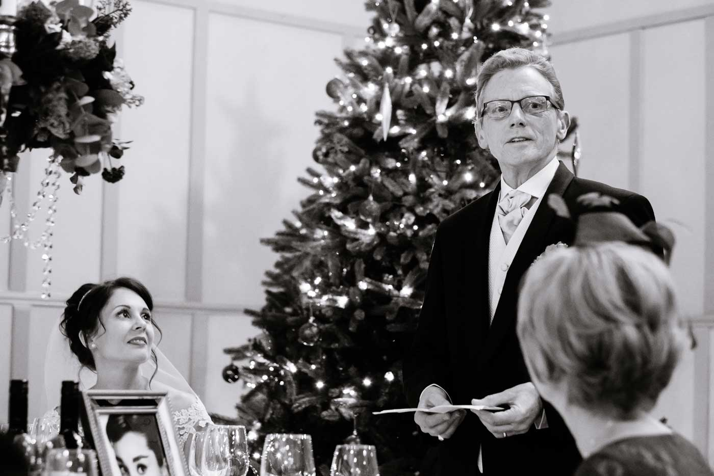 Close-up of father giving his speech as bride looks on by Stanbrook Abbey wedding photographer Clive Blair Photography