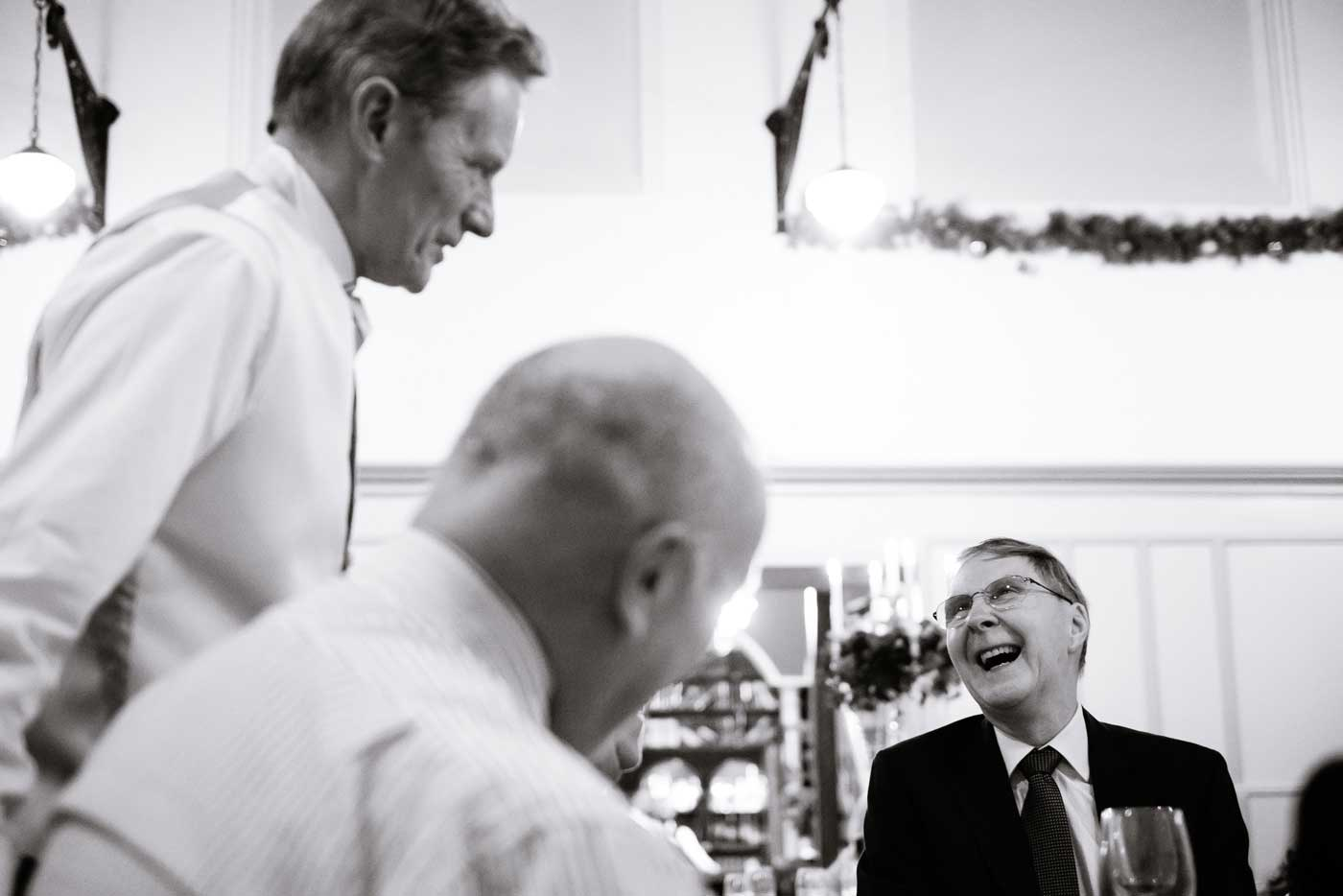 Laughing man during wedding breakfast in St Anne's Hall at Stanbrook Abbey