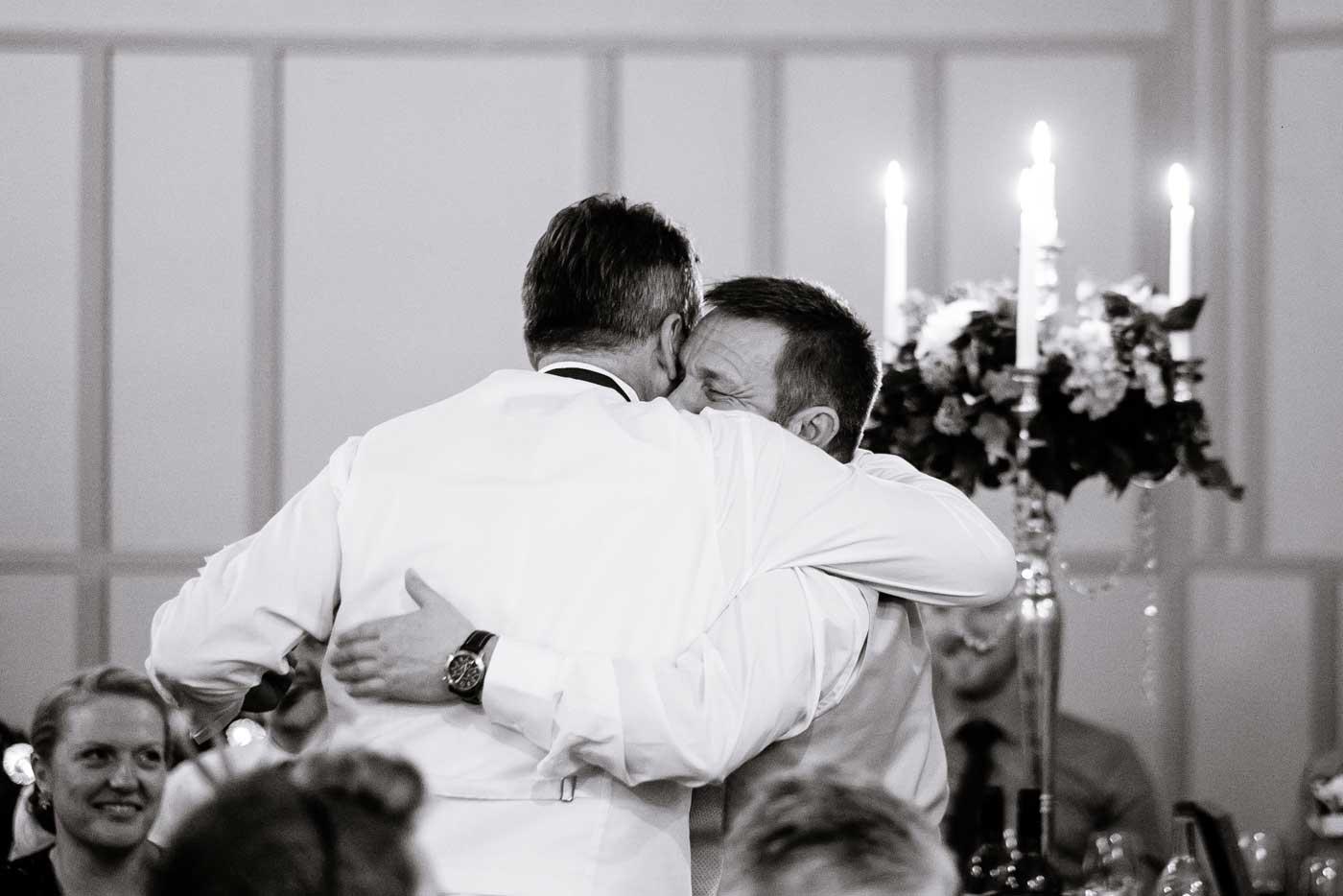 Groom hugging guest after his speech
