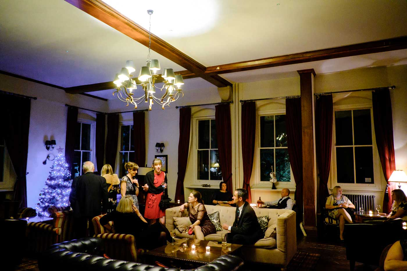 Guests's relaxing in the Piano Lounge at Stanbrook Abbey by Stanbrook Abbey wedding photographer Clive Blair Photography