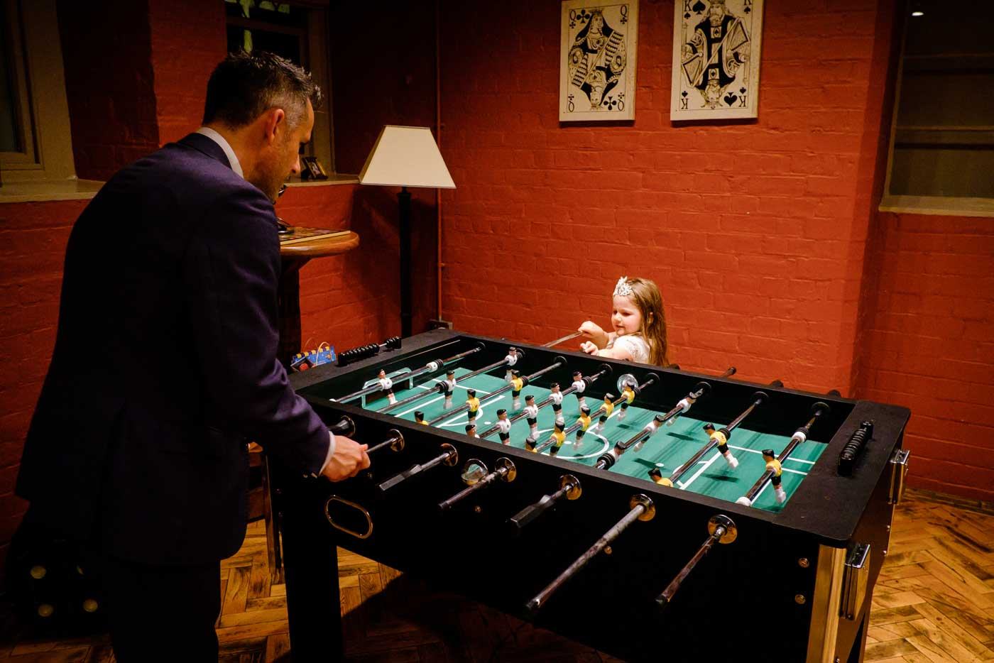 Man and his young daughter playing table football in the basement games room at Stanbrook Abbey