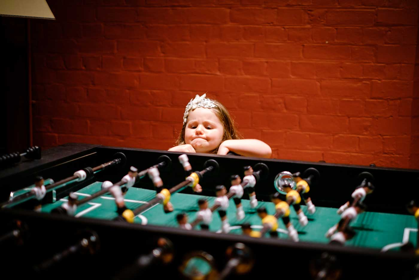 Young girl determined not to be beaten at table football by Stanbrook Abbey wedding photographer Clive Blair Photography
