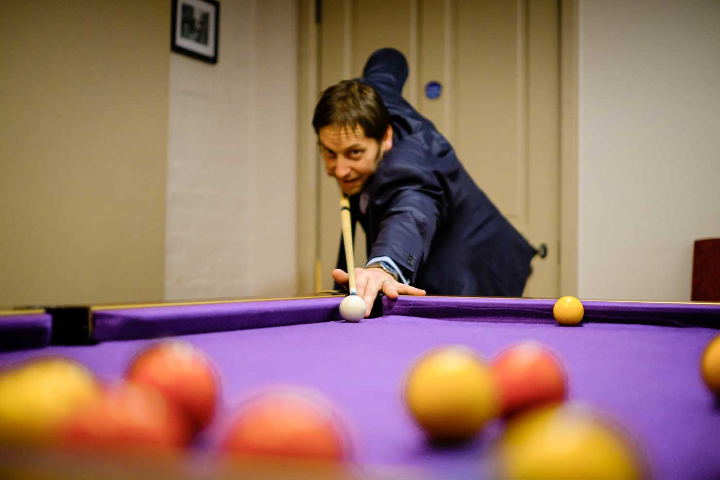 Man playing pool in the basement games room at Stanbrook Abbey by Stanbrook Abbey wedding photographer Clive Blair Photography