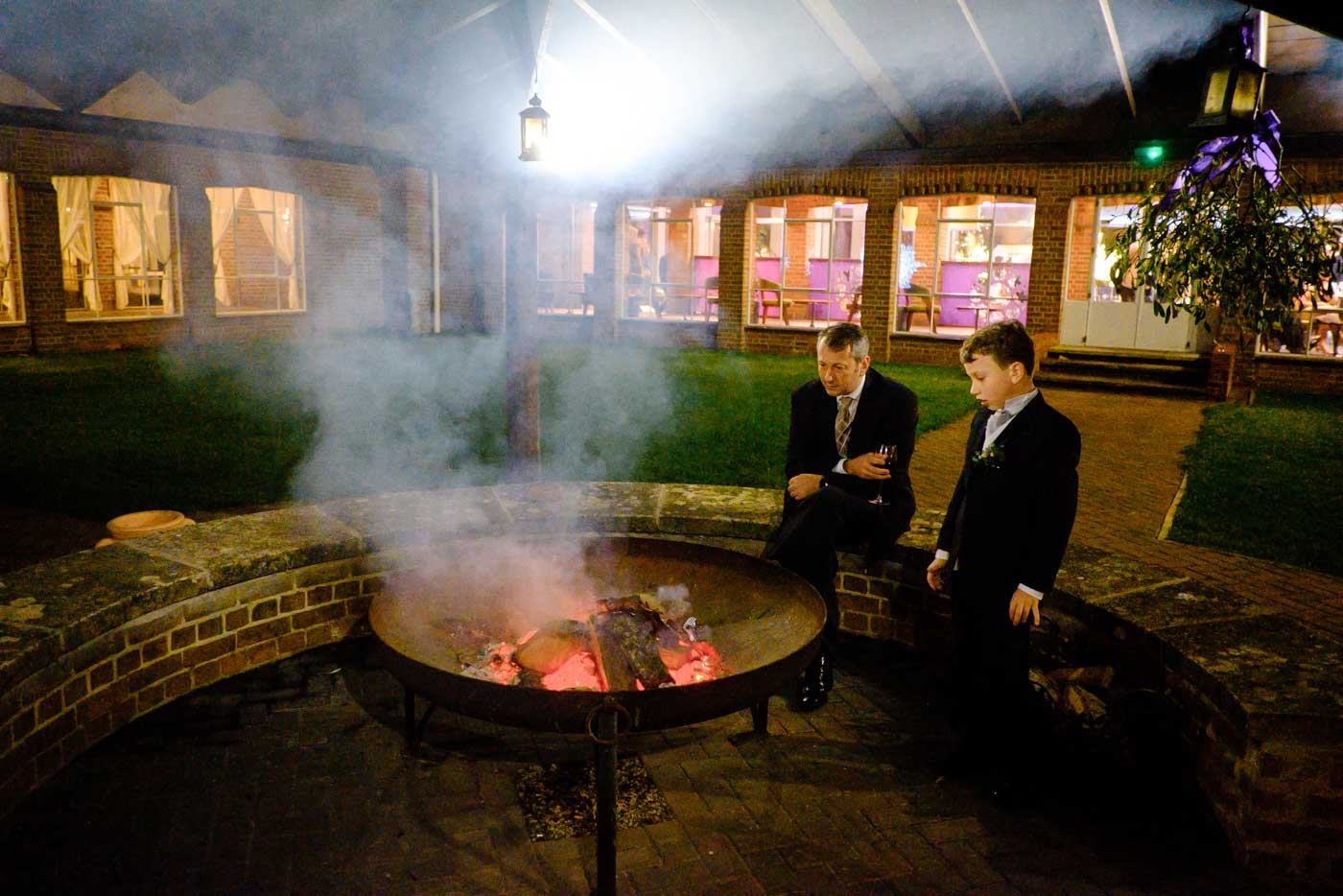 Man and his son by firepit in the outside courtyard of Stanbrook Abbey during a winter wedding