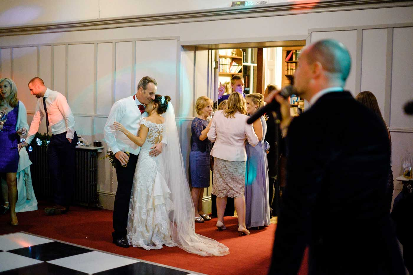 Bride and groom hugging during their eveing wedding reception by Stanbrook Abbey wedding photographer Clive Blair Photography