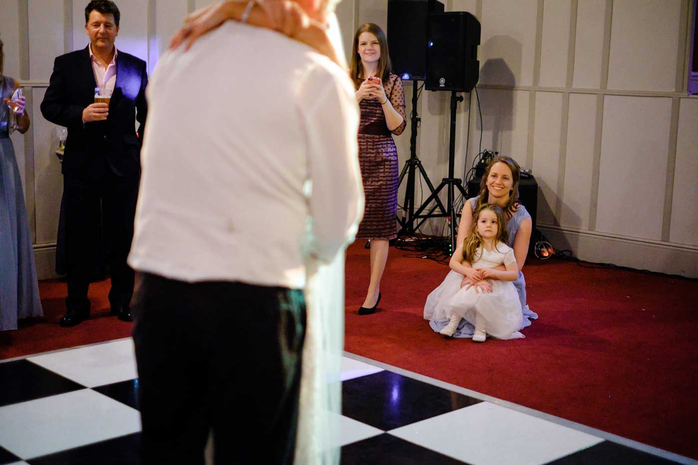 Maid and flowergilr watching bride and groom during their first dance by Stanbrook Abbey wedding photographer Clive Blair Photography