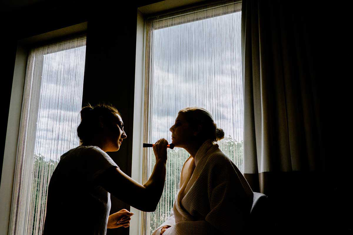 Bride having her makeup put on before her Old Library wedding ceremony