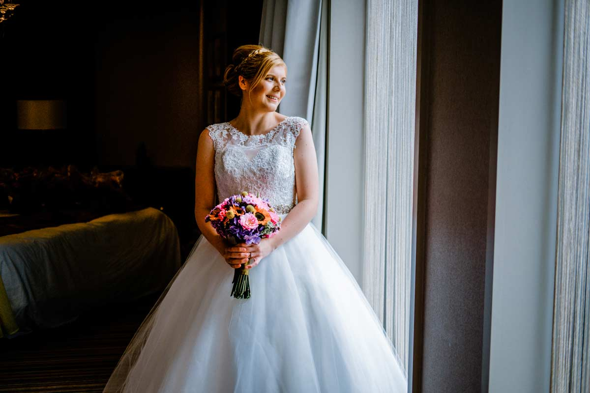 Bride looking out window before her wedding ceremony