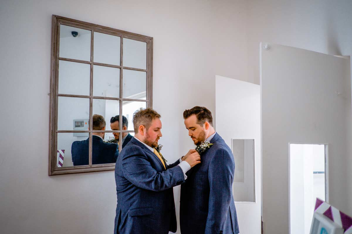 Groom having his buttonhole adjusted