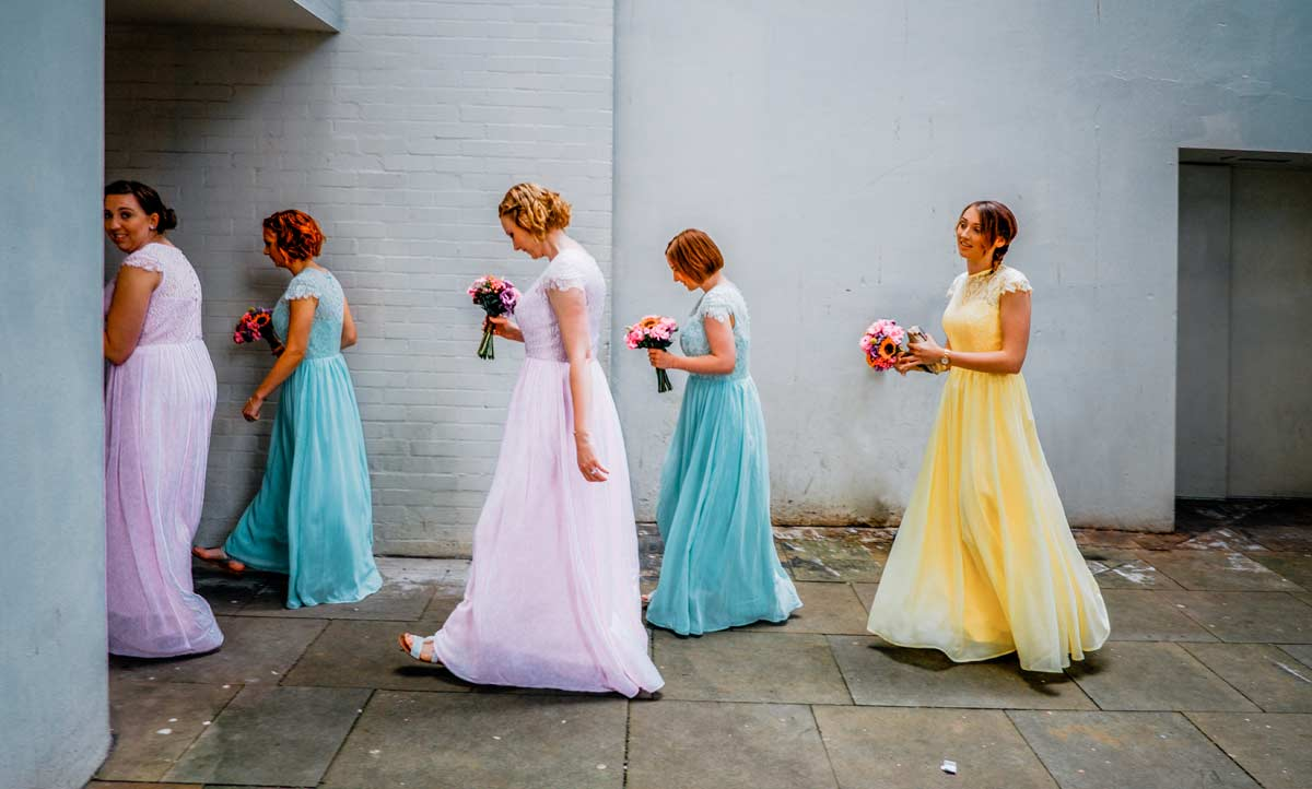 Bridesmaid in pastel colours walking to wedding ceremony room
