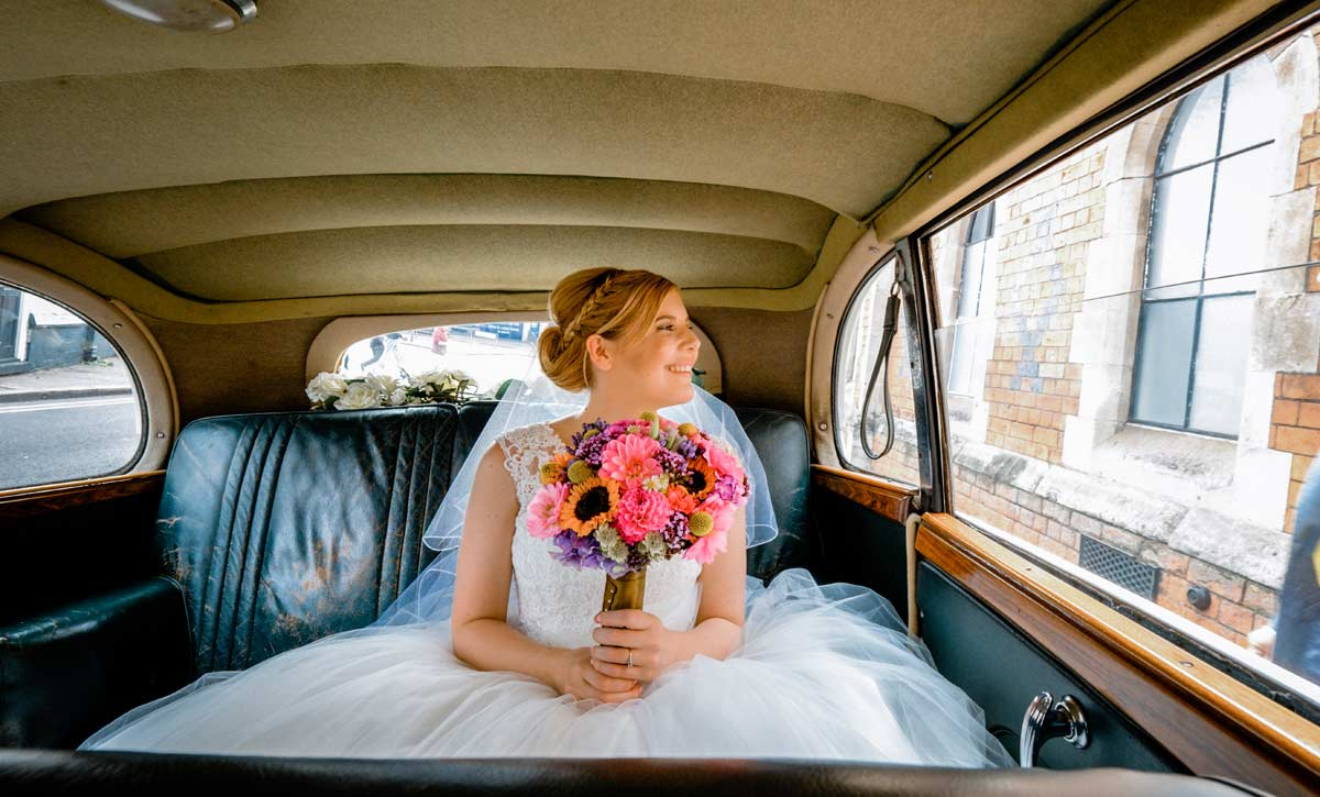 Bride in wedding car by documentary wedding photographer Birmingham Clive Blair Photography