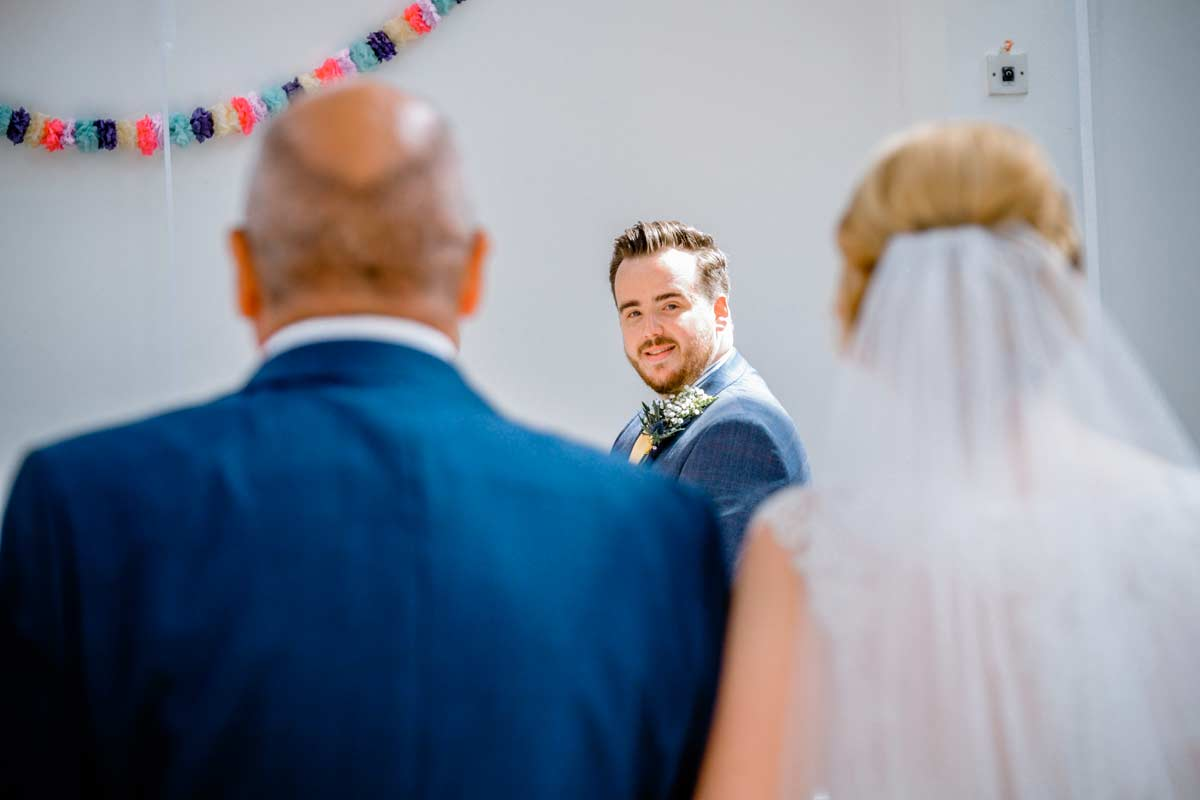 Groom seeing his bride for the first time at his wedding