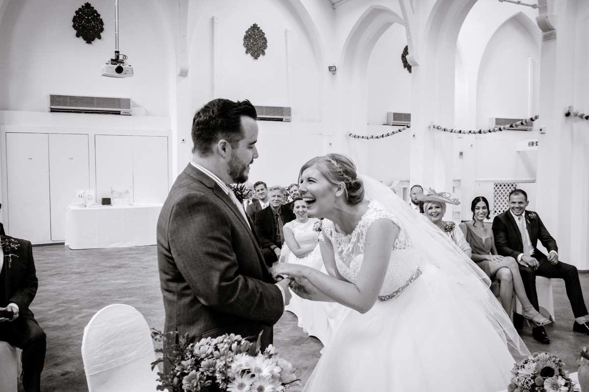 Bride laughing as exchanging rings