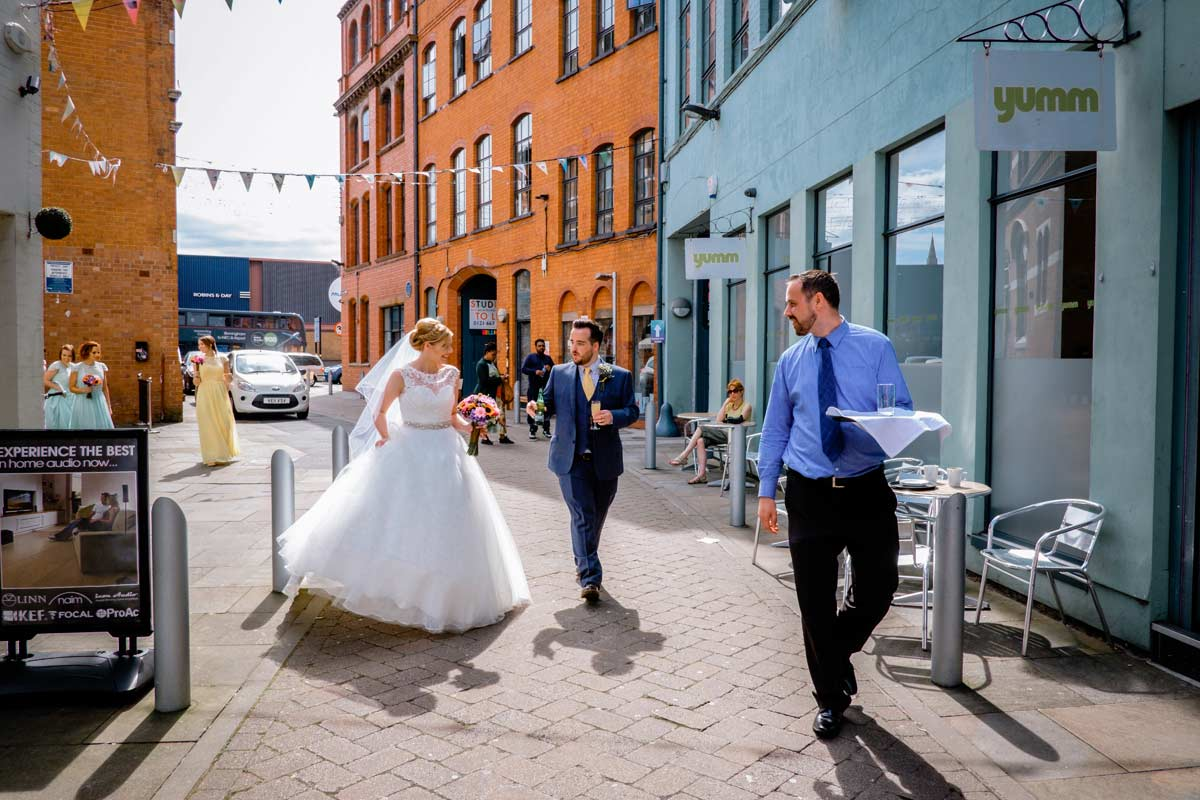 Bride and groom walking in The Custard Factory