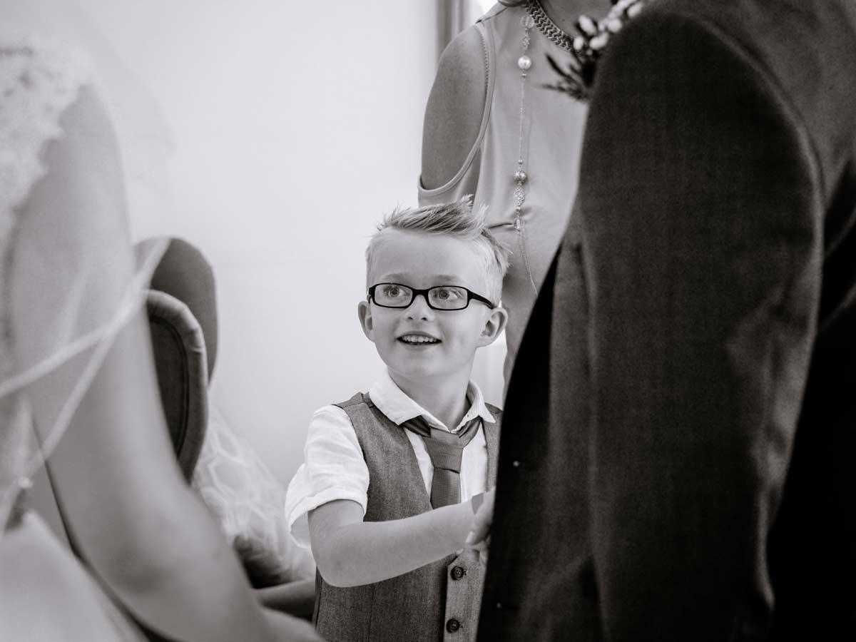 Boy in glasses smiling at bride