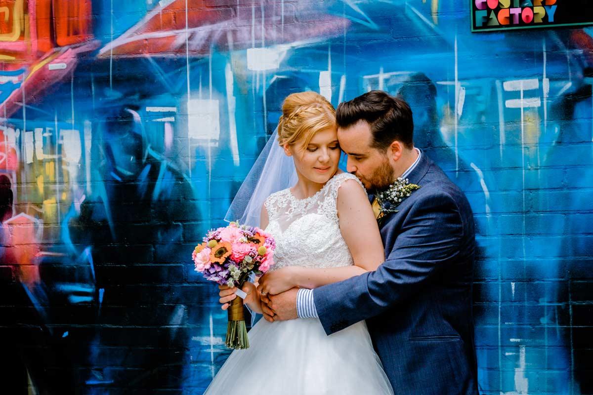 Groom tenderly kissing his bride on her shoulder