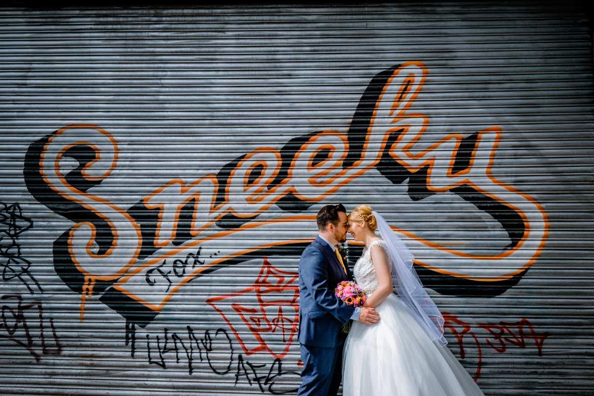 Bride and groom by Sneeky Fox graffiti near The Custard Factory