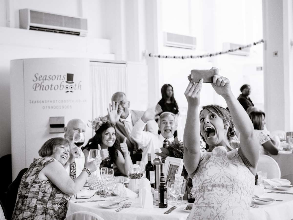 Woman and guests taking a selfie at an old library wedding