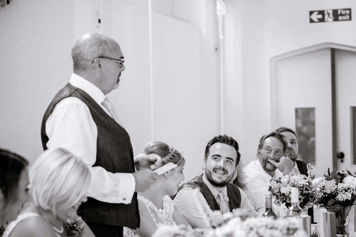 Groom listening to his father in laws speech at his old library wedding