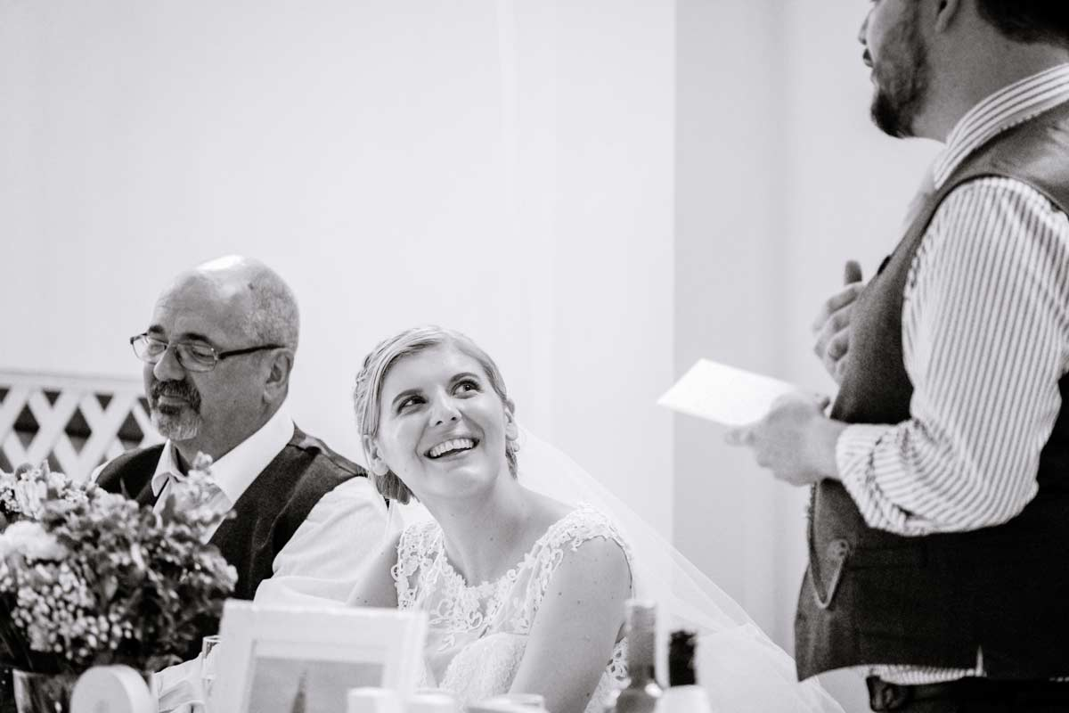 Bride listening to her husband give his speech
