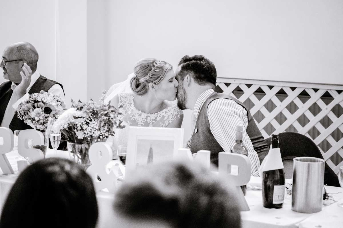 Bride tenderly kissing groom after his speech by documentary wedding photographer Clive Blair