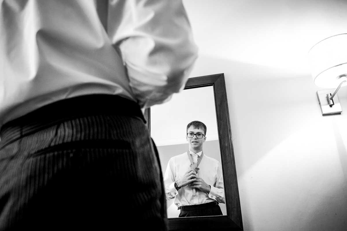 Groom tieing his tie
