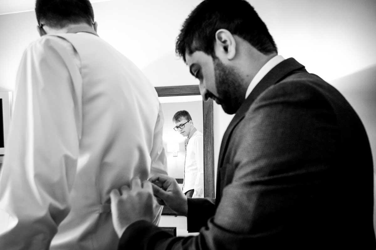 Grooms man helping groom get ready
